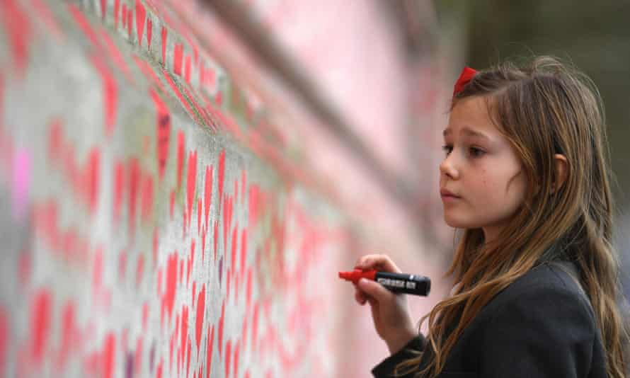 A girl adds a heart to the National Covid Memorial Wall in London.