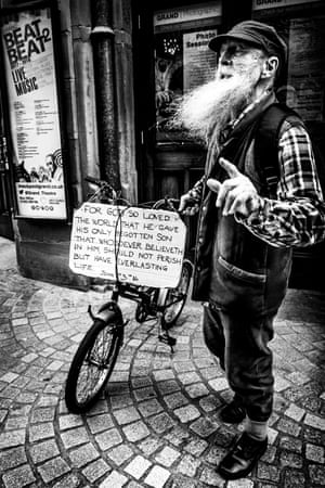 Man with bicycle and religious notice on a street in Blackpool