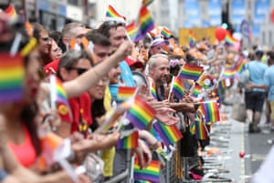People wave rainbow flags as they watch the parade