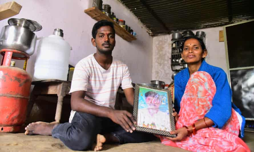 Latha Bollapally, with her son Rajesh Goud, holds a picture of her husband, Madhu Bollapally, 43, a migrant worker who died in Qatar