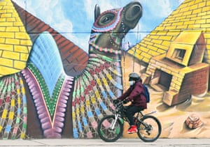 A person wearing a mask cycles past a climate change-themed nature mural on Earth Day during the Covid-19 pandemic in Toronto, Canada.