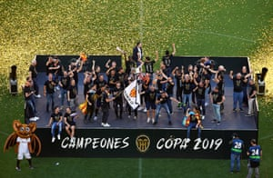 Valencia players celebrate with the Copa del Rey trophy at the Mestalla during their victory parade.