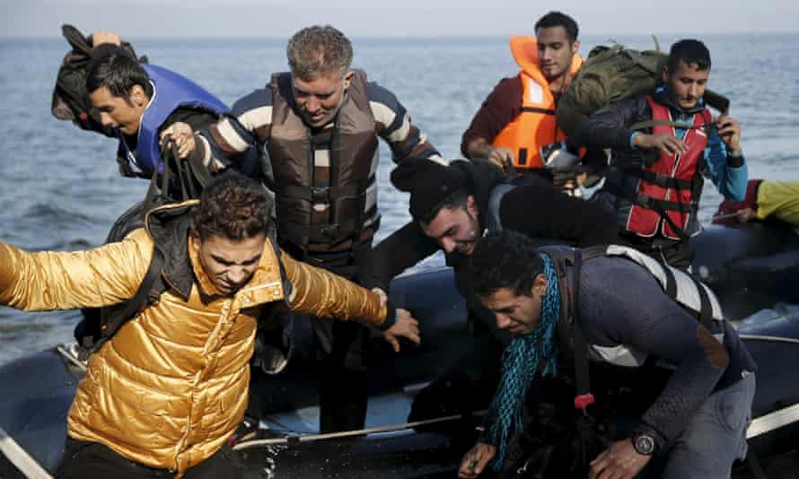 People jump off an inflatable raft as they arrive on the Greek island of Lesbos from Turkey.