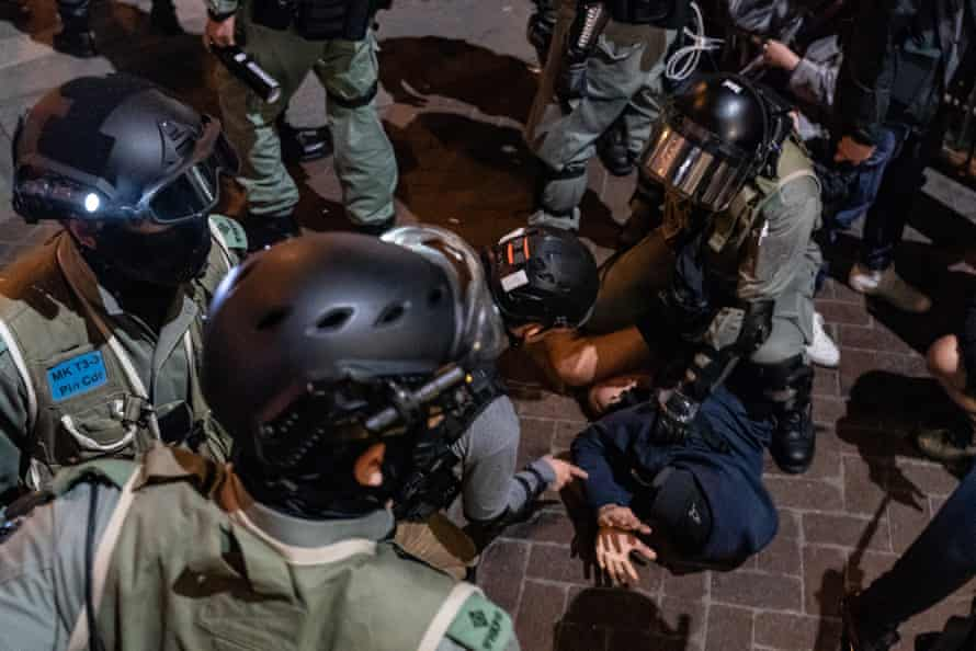 A man is detained by riot police in Mongkok.