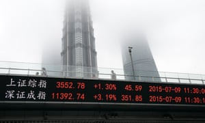 In this July 9, 2015 photo, people walk on a footbridge with an electronic stock ticker showing real time stock market indices at Lujiazhui Financial and Trade Zone in Shanghai.