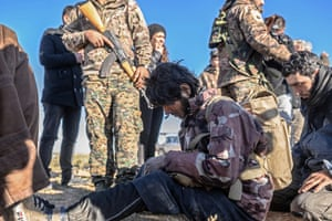 Members of the Kurdish-led Syrian Democratic Forces (SDF) prepare to search men and boys suspected of being Islamic State (IS) group fighters, after leaving the IS group's last holdout of Baghouz, in the eastern Syrian Deir Ezzor provinc