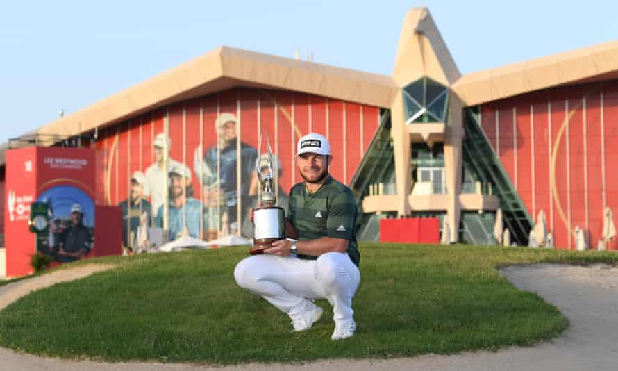Tyrrell Hatton poses for with the trophy following victory at the Abu Dhabi Championship