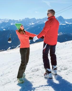 Couple holding hands on ski slope