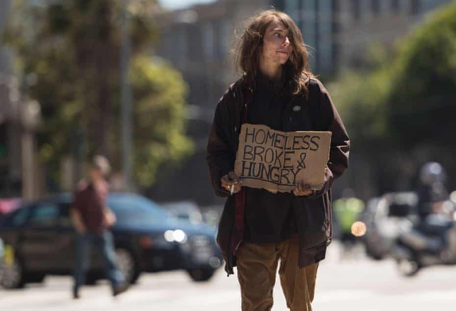 A homeless man begs on a center divider in San Francisco, California