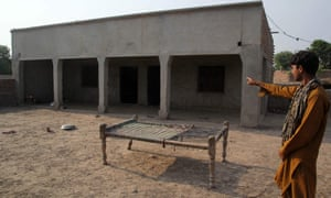 A villager points to a house near Multan in Punjab province where a teenage girl was raped as punishment for a sexual assault allegedly committed by her brother