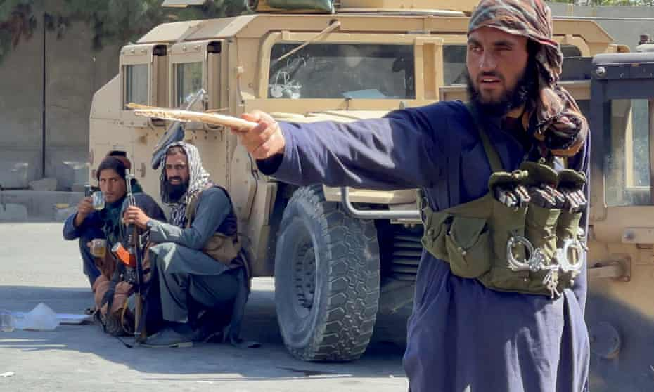 Taliban forces block the roads around the airport in Kabul on Friday