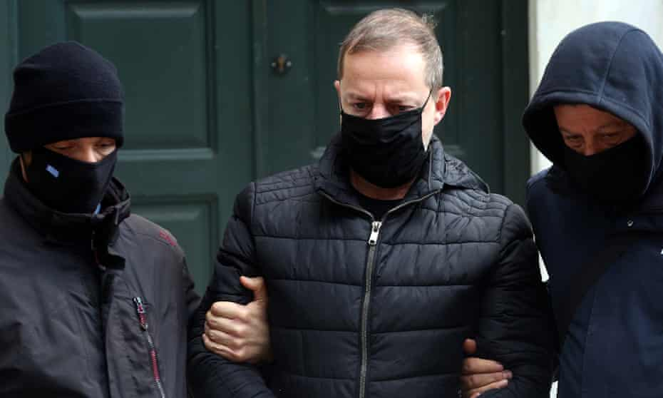 Dimitris Lignadis is escorted out of the prosecutor's office in Athens, 21 February.