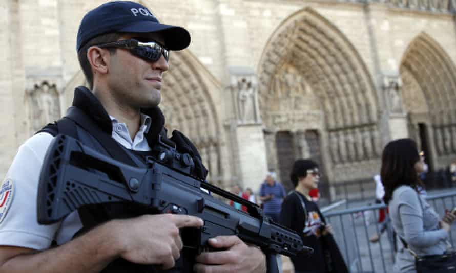 A French police officer patrols in front of Notre Dame cathedral, in Paris.