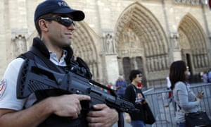 An armed officer looks on as tourists pass outside the Notre Dame cathedral