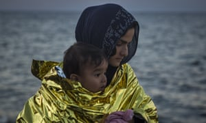A woman wearing a thermal blanket holds her child on a beach in Lesbos