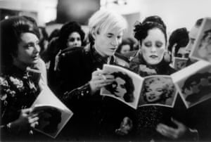 Andy Warhol with Jane Forth, teenage star of his film Trash, signing autographs at the Tate Gallery.