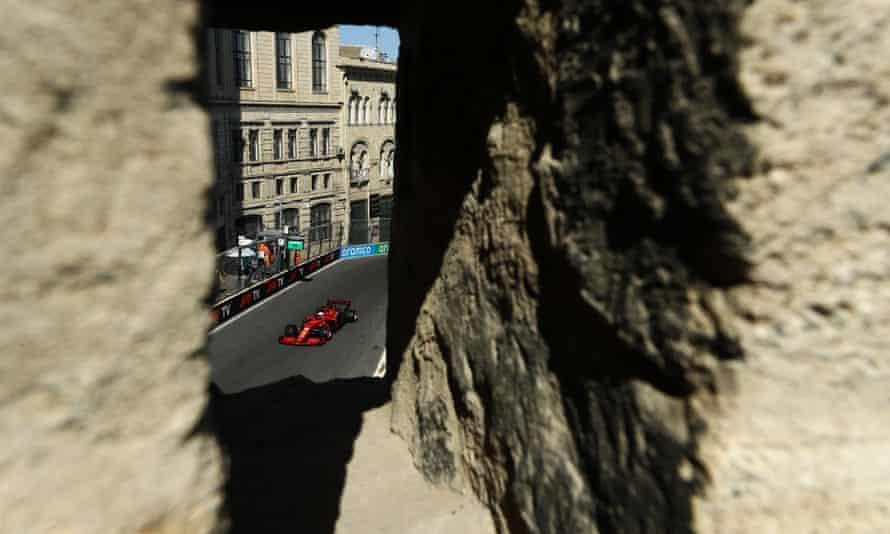 Ferrari's Charles Leclerc captured through a hole in a wall