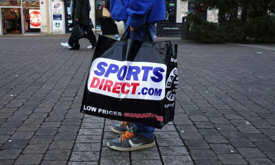 A shopper holds a Sports Direct bag