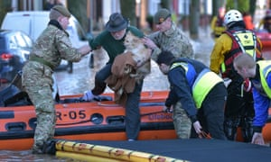 A rescue team helps evacuate people from their homes after Storm Desmond caused flooding on 6 December 2015 in Carlisle