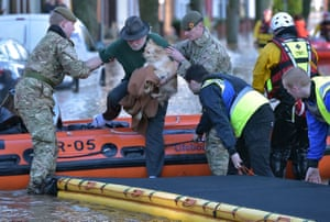 A rescue team helps to evacuate a man and his dog in Carlisle