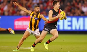 Zach Merrett runs from Paul Puopolo during the match between the Essendon Bombers and the Hawthorn Hawks at the MCG on Saturday.