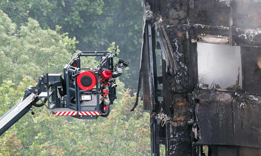 Platform with hoses and cameras alongside exterior of Grenfell Tower