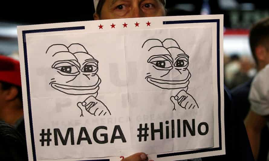 A Trump supporter holds a Pepe the Frog sign, a symbol that has become an emblem of the alt-right movement.