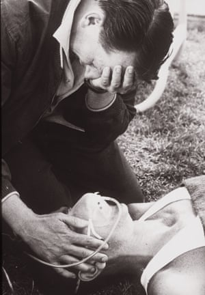 Black and white photo.  Close up of two men, above one cradles his face head looking down, as he touches the cheek of a prostrate runner in an oxygen mask.