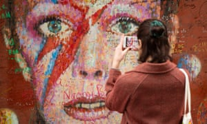 A woman photographs messages written on the David Bowie mural in Brixton, south London