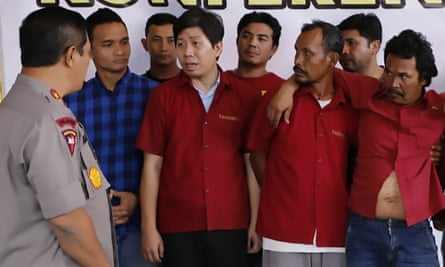 Police inspector Agus Andrianto, left, questions a group of men arrested over the murder of two journalists