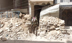 Syrian soldiers enter a damaged house in Palmyra.