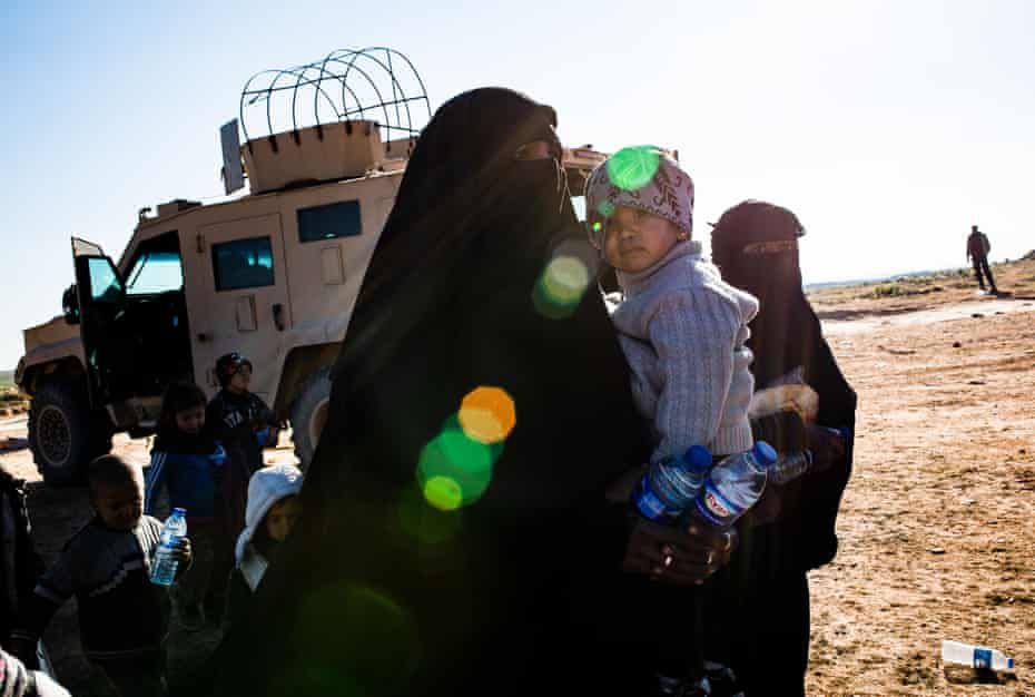 A woman and her son are seen near the city of Baghuz