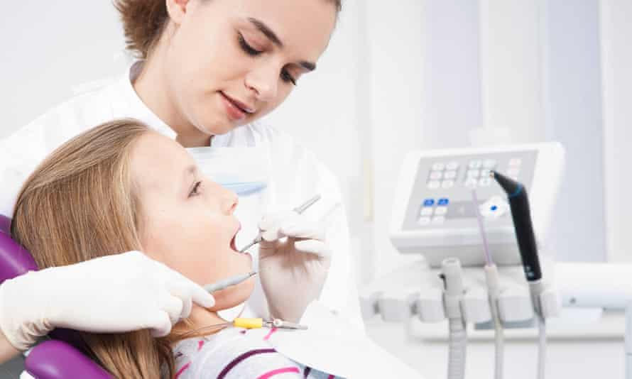 A dentist checks a girl's teeth