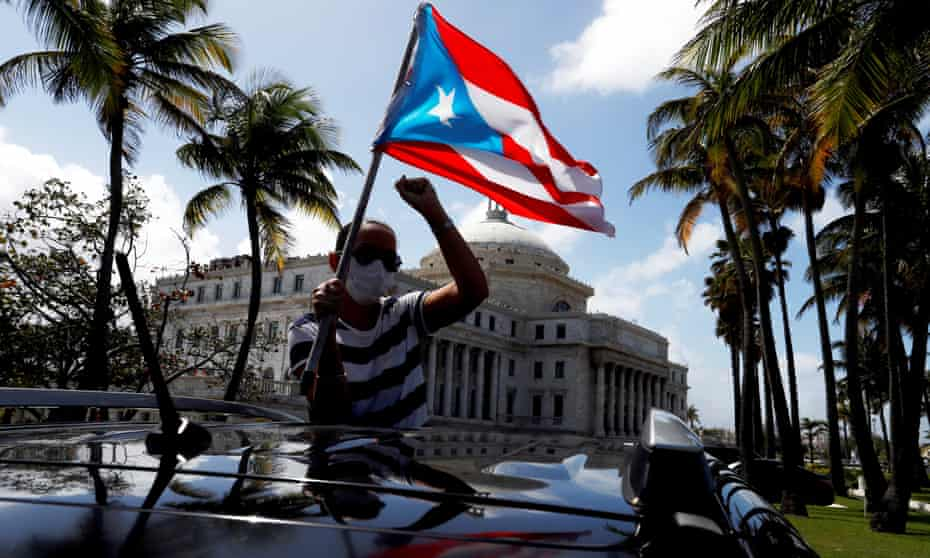 A man holds a Puerto Rican national flag during a protest against the school reopening this week. Over the past half century Puerto Rico has held six non-binding referendums on its status.