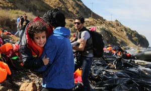 People are assisted moments after they arrive with other Syrian and Iraqi refugees on the island of Lesbos from Turkey