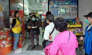 People queue up to buy face masks at a pharmacy in Taipei, Taiwan