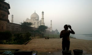 A man washes himself by the river Ganges on a chilly morning in front of the Taj Mahal, in the city of Agra.