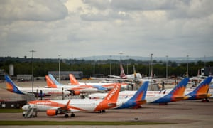 BRITAIN-IRELAND-HEALTH-VIRUS-AVIATION<br>Aircraft grounded due to the COVID-19 pandemic, including planes operated by TUI, EasyJet and Jet2, are pictured on the apron at Manchester Airport in Manchester, north west England on May 1, 2020. - Irish low-cost carrier Ryanair said on Friday it planned to axe 3,000 pilot and cabin crew jobs, or 15 percent of staff, with air transport paralysed by coronavirus. Dublin-based Ryanair added in a statement that most of its flights would remain grounded until at least July and predicted it would take until summer 2022 at the earliest before passenger demand recovers. (Photo by Oli SCARFF / AFP) (Photo by OLI SCARFF/AFP via Getty Images)