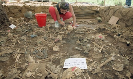 A forensic anthropologist brushes dirt from human remains in El Mozote in 1992. Campaigners hope that the reopening of the case will bring the killers to justice.
