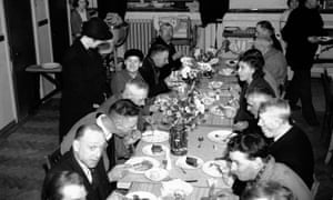 People sit down for a meal for sixpence in West Ham, London, 1940.