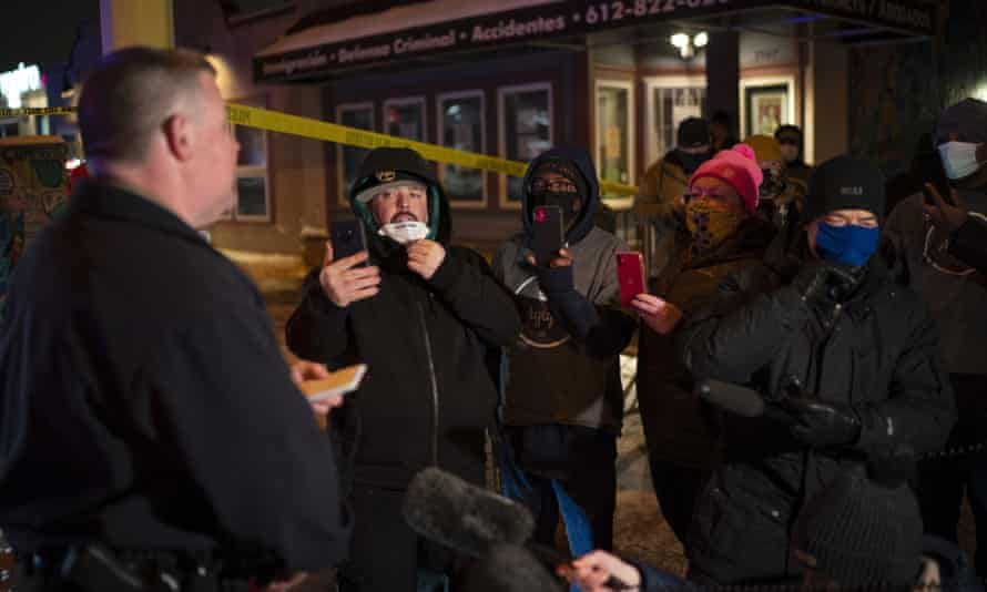 Minneapolis Police spokesman John Elder briefs community members and others about the shooting