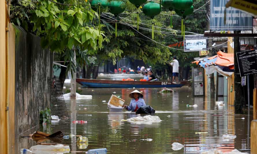 A woman wades past buildings flooded by Typhoon Damrey in the town of Hoi An in Vietnam's south-central coast region
