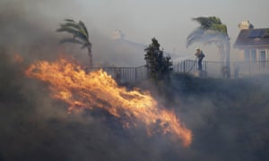 A firefighter sprays water in front of an advancing wildfire on Friday in Porter Ranch, California.