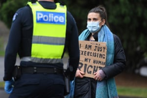 A woman with signs of speaking to police during a protest in Melbourne.