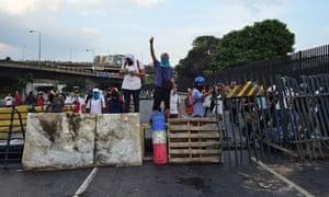 Venezuelan opposition activists stand behind a barricade set up during a demonstration in Caracas.