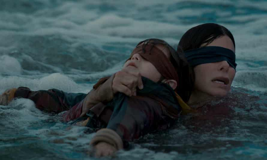 A blindfolded woman swims through raging water carrying a blindfolded boy