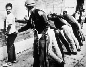 Police frisk an African American man as other suspects lean against wall in Detroit, 1967.