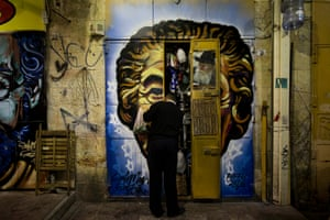 A shop owner closes the shutters of his stall decorated with a portrait of former Israeli prime minister Golda Meir