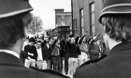 National Front supporters give a Nazi salute to  a police cordon, east London, 1979.
