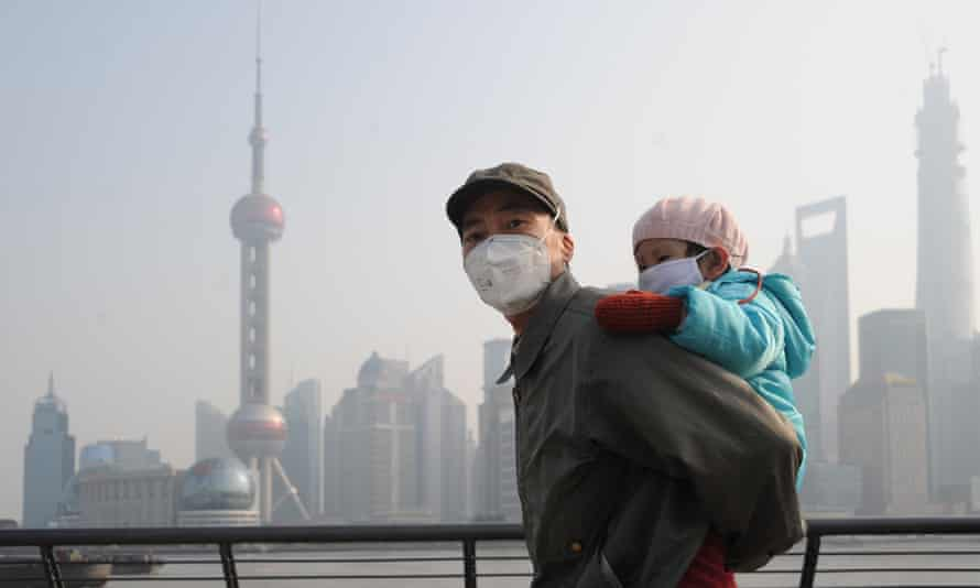 A man and his child wear masks to protect them from heavy smog as they visit Waitan in December 2013 in Shanghai, China.